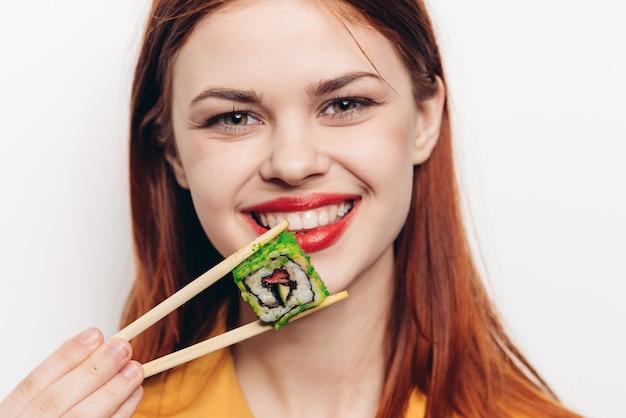 Kobieta je kolorowe bułki bambusowymi pałeczkami, azjatyckie jedzenie, jasne tło