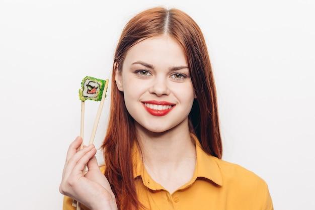 Kobieta je kolorowe bułki bambusowymi pałeczkami, azjatyckie jedzenie