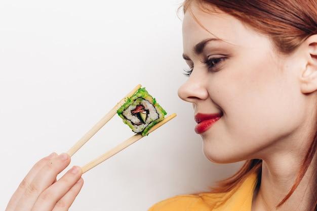 Kobieta je kolorowe bułki bambusowymi pałeczkami