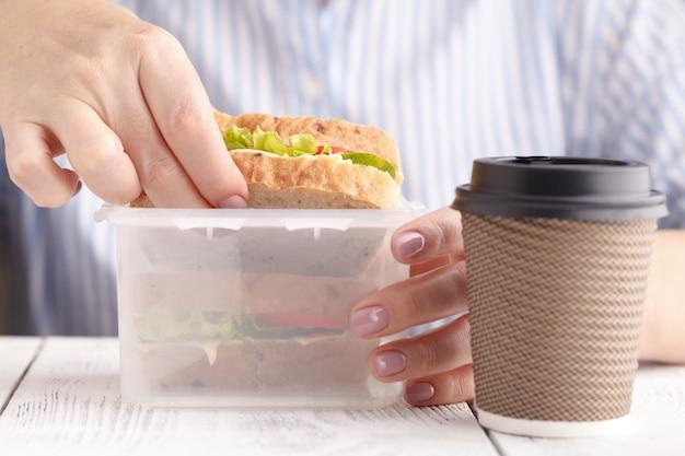 Kobieta je łososiową panini kanapkę z pomidorami i serem przy pracą