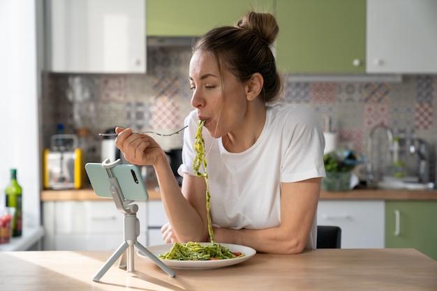 Kobieta je makaron z wegetariańskim sosem pesto, oglądając film na smartfonie na statywie w domu.