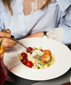 Kobieta je papilotkę sałatki z pomidorami - owoce morza ze świeżymi krewetkami, sercówki z pikantnym sosem -