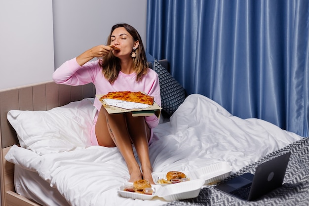 Kobieta je pizzę w domu