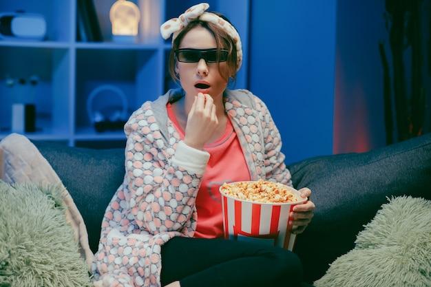 Kobieta je popcorn w szkłach 3d. zabawa młoda kobieta w okularach 3d oglądając film, jedz popcorn.
