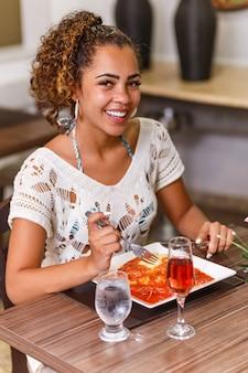 Kobieta je pyszne danie z mięsa i makaronu parmigiana.