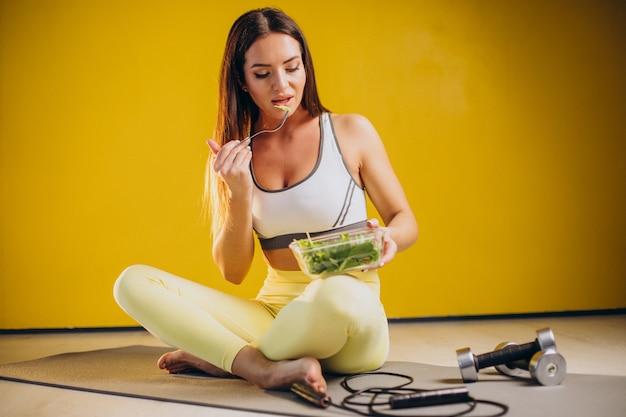 Kobieta je sałatka na białym tle na żółtym tle
