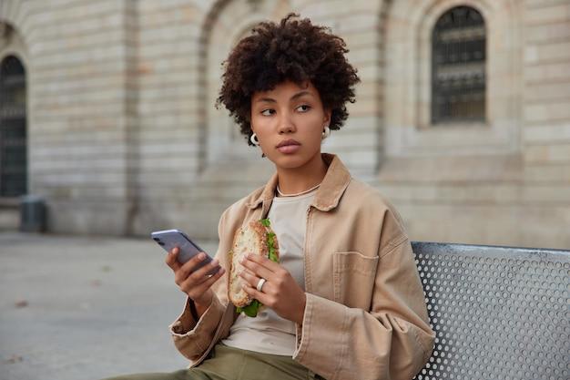 Kobieta je smaczną kanapkę i korzysta z telefonu komórkowego odpoczywa po przejściu przez miasto pozuje na zewnątrz na ławce skoncentrowana w oddali