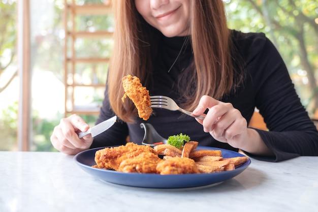 Kobieta je smażonego kurczaka i frytki w restauracji