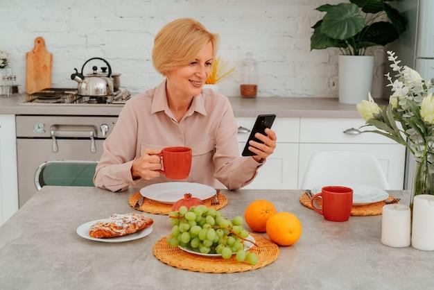Kobieta je śniadanie w domu z owocami, ciastem i kawą i czyta wiadomości ze swojego smartfona