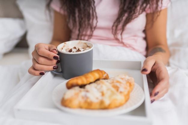 Kobieta je śniadanie w łóżku w jasnym apartamencie hotelowym lub w domu. okno światła portret młodej dziewczyny jedzenie rogalika i picia kawy.