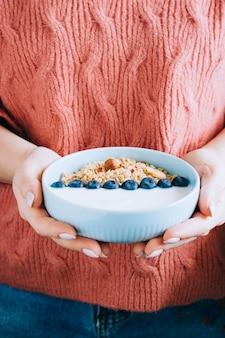 Kobieta je śniadaniowego puchar z muesli, jogurtem, jagodami i orzechami laskowymi w koralowym woolen pulowerze