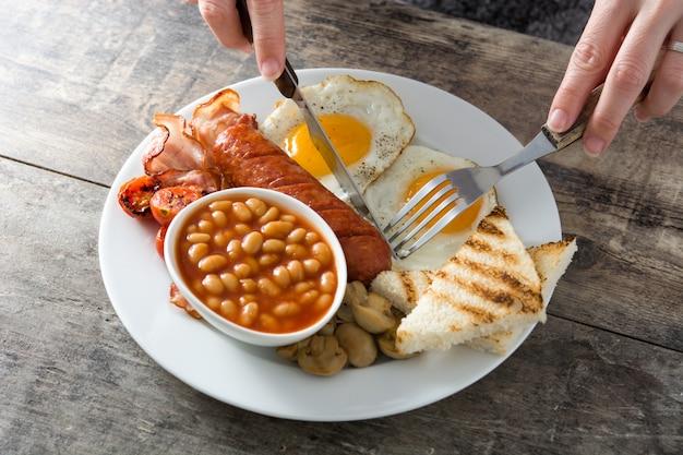 Kobieta je tradycyjne pełne angielskie śniadanie ze smażonymi jajkami, kiełbasami, fasolą, pieczarkami, grillowanymi pomidorami i boczkiem na białej drewnianej powierzchni
