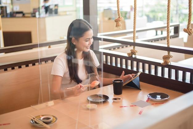 Kobieta je w restauracji z protokołem dystansowania społecznego podczas blokady miasta z powodu pandemii koronawirusa