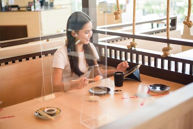 Kobieta je w restauracji z protokołem dystansu społecznego