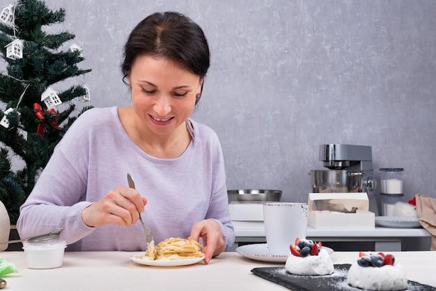 Kobieta je w swojej kuchni. śniadanie z deserem.