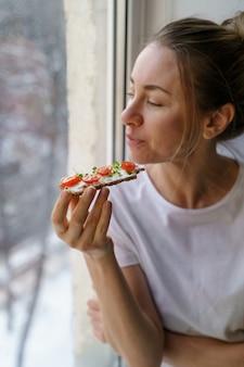 Kobieta je żytni chleb chrupki z kremowym tofu z wegetariańskim serem, pomidorem, mikro zieleniną. zdrowe jedzenie