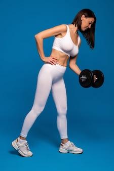 Kobieta jedno ramię biceps curl z hantlami na niebieskiej powierzchni
