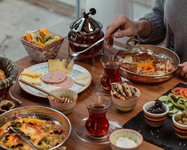 Kobieta jedząca omlet śniadaniowy na patelni, wokół stołu podarowanego oliwkami, serem, salami, słodyczami, warzywami i czarną herbatą.
