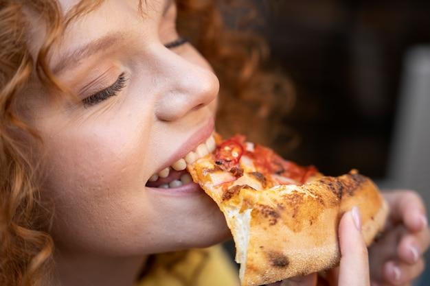 Kobieta jedząca pizzę z bliska