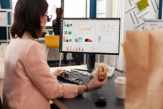 Kobieta jedząca smaczną kanapkę po przerwie na posiłek pracująca w firmie biznesowej