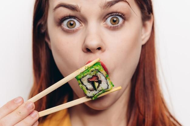 Kobieta jedzenie bułek z bambusowymi pałeczkami