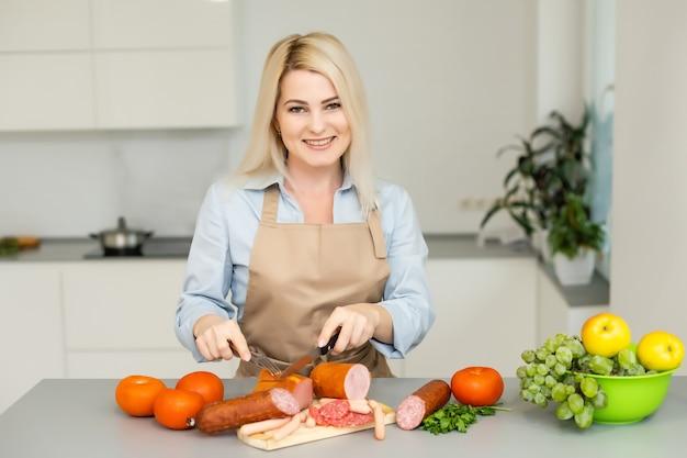 Kobieta jedzenie kiełbasy w kuchni