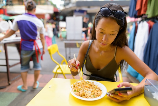 Kobieta jedzenie makaronu pad thai przy drodze khao san