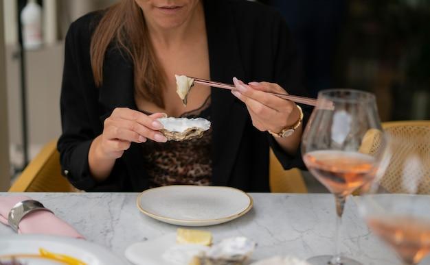 Kobieta jedzenie ostryg pałeczkami siedzi przy stole przed restauracją. pojęcie luksusu