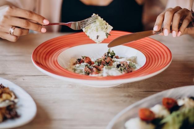 Kobieta jedzenie ravioli we włoskiej restauracji