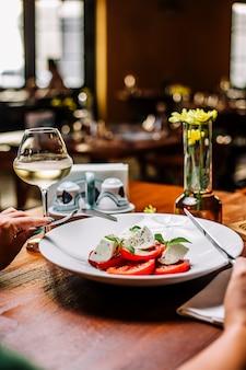 Kobieta jedzenie sałatka pomidorowa z mozzarellą i miętą podawane z białym winem