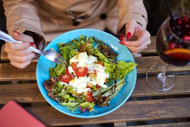 Kobieta jedzenie sałatki i picie sangrii w street cafe wieczorem relaks po ciężkim dniu pracy