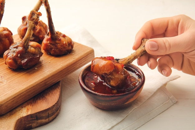 Kobieta jedzenie smaczne lizaki z kurczaka z sosem na jasnej powierzchni drewnianych