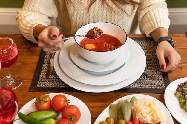 Kobieta jedzenie smacznej zupy z barszczu czerwonego