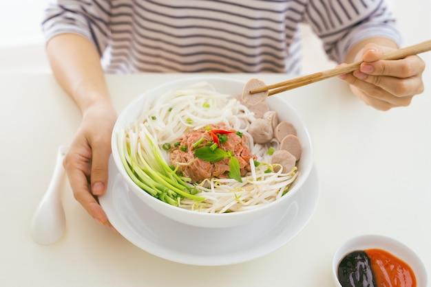 Kobieta jedzenie tradycyjnego wietnamskiego makaronu pho przy użyciu pałeczek.