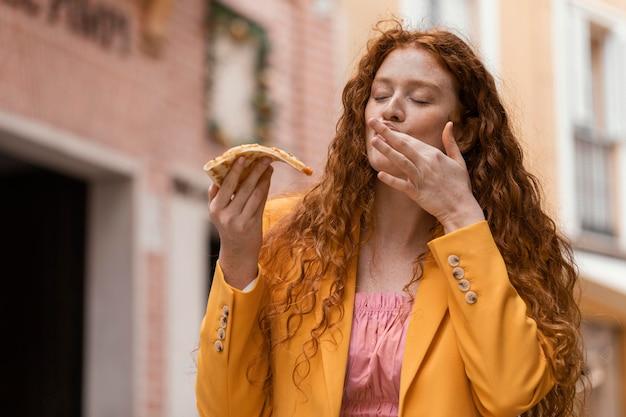 Kobieta jedzenie ulicznego jedzenia na zewnątrz