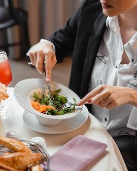 Kobieta jedzenie wędzonej sałatki z łososia z rukolą i koperkiem w restauracji