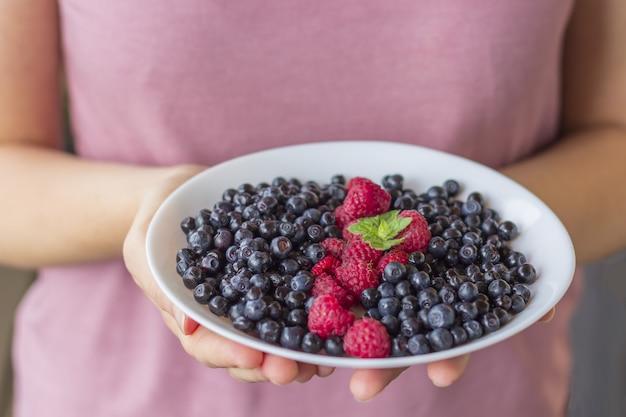 Kobieta jedzenie zdrowej żywności. młoda dziewczyna w odzieży sportowej trzyma talerz świeżych jagód.
