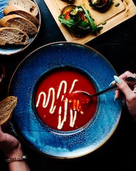 Kobieta jedzenie zupa pomidorowa z roztopionym parmezanem wewnątrz niebieski talerz.