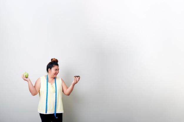 Kobieta jedzenie żywności na szarej ścianie