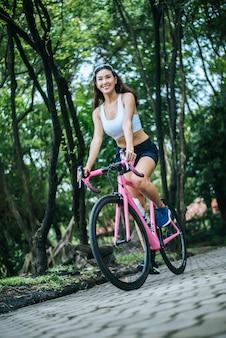 Kobieta jedzie drogowego rower w parku. portret młoda piękna kobieta na menchia rowerze.