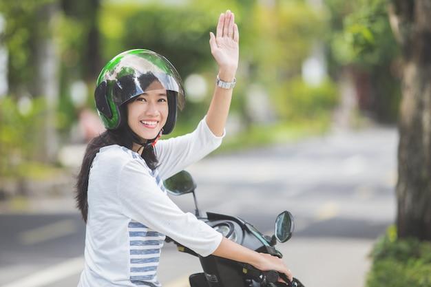Kobieta jedzie motocykl i macha ręką