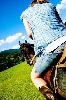 Kobieta jedzie na brązowym koniu