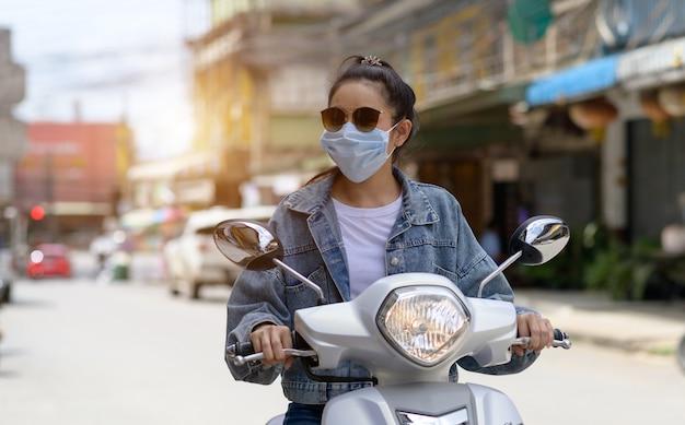 Kobieta jedzie na motocyklu w masce w mieście