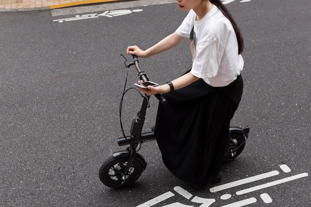 Kobieta jedzie na rowerze elektrycznym po mieście i trzyma smartfon