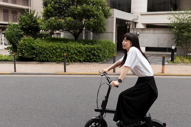 Kobieta jedzie na rowerze elektrycznym po mieście