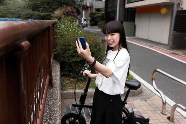 Kobieta jedzie na rowerze po mieście i robi selfie