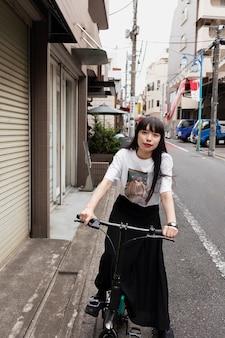 Kobieta jedzie na skuterze elektrycznym w mieście