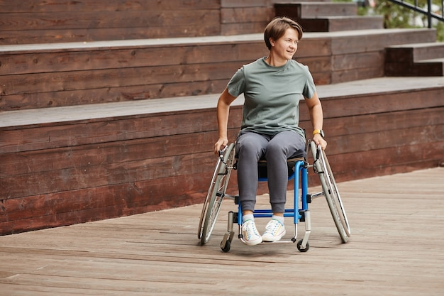 Kobieta jedzie na wózku inwalidzkim na zewnątrz