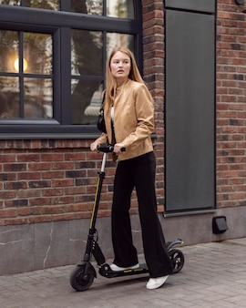 Kobieta jedzie na zewnątrz skuterem elektrycznym