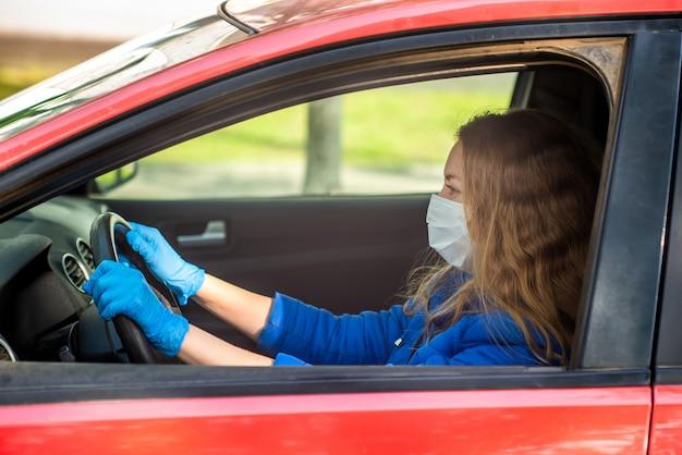 Kobieta jedzie samochód w ochronnej medycznej masce i rękawiczkach. styl życia i bezpieczna jazda podczas pandemicznego koronawirusa